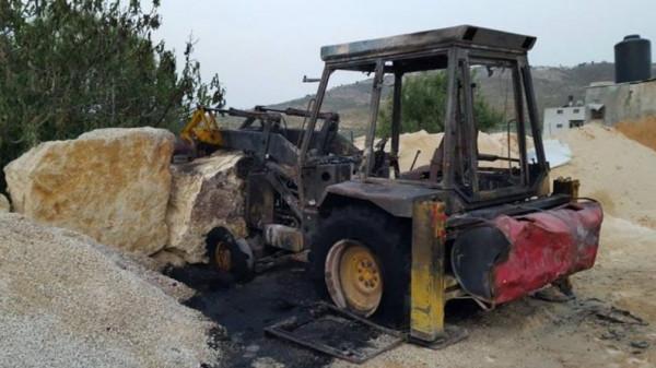 مستوطنون يحرقون جرافة ويخطون شعارات عنصرية جنوب نابلس