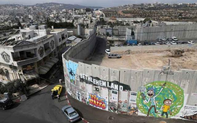 منظر عام يظهر كتابات على الجدار الفاصل في مدينة بيت لحم بالضفة الغربية