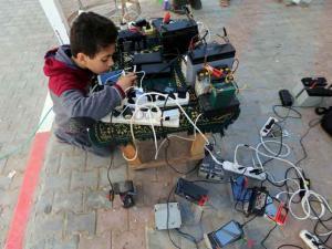 فتى فلسطيني يشحن الهواتف المحمولة بالمجان بسبب ازمة الكهرباء في غزة