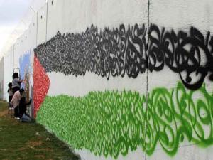 فنانون لبنانيون يرسمون العلم الفلسطيني على جدار على حدود بلادهم مع اسرائيل