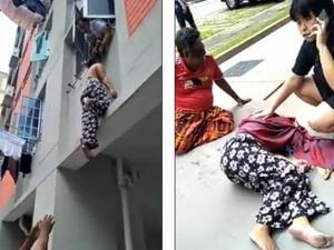 رجل يمسك امرأة من شعرها لمنع سقوطها من بناية (شاهد)